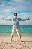 圣诞老人帽子的人在热带海滩 免版税库存图片
