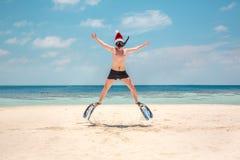 圣诞老人帽子的人在热带海滩 免版税库存照片