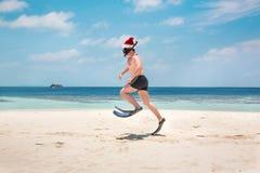 圣诞老人帽子的人在热带海滩 免版税图库摄影
