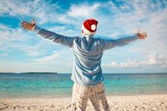 圣诞老人帽子的人在热带海滩 库存图片