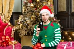 圣诞老人帽子的人有在圣诞树的香槟瓶的 库存照片