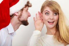 圣诞老人帽子的人耳语对妇女耳朵 免版税库存图片