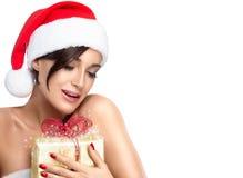 圣诞老人帽子的华美的圣诞节女孩有一件不可思议的金黄礼物的 图库摄影