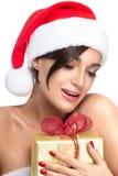 圣诞老人帽子的华美的圣诞节女孩有一件金黄礼物的 免版税库存照片