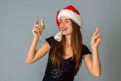 圣诞老人帽子的华美的女孩有杯的香槟 免版税库存图片