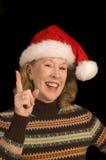 圣诞老人帽子的可爱的中年妇女 免版税库存照片