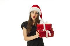 圣诞老人帽子的可爱的妇女有红色礼物的 库存图片