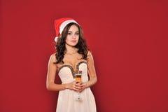 圣诞老人帽子的可爱的妇女有玻璃的 库存照片