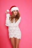 圣诞老人帽子的可爱的妇女,在桃红色的演播室 免版税库存照片