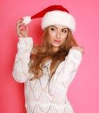 圣诞老人帽子的可爱的妇女,在桃红色的演播室 库存照片