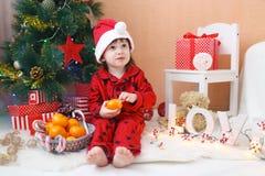 圣诞老人帽子的可爱的小男孩用蜜桔 库存照片