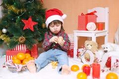圣诞老人帽子的可爱的小男孩用蜜桔 免版税库存照片