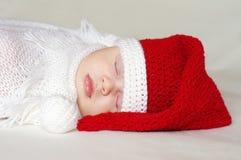 圣诞老人帽子的可爱的睡觉的婴孩 库存图片