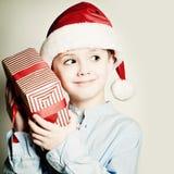 圣诞老人帽子的圣诞节孩子 愉快的小男孩和Xmas箱子 库存图片