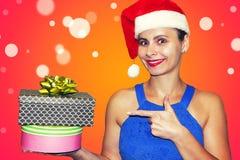 圣诞老人帽子的圣诞节少妇在两个礼物盒指向 愉快的女孩Xmas假日 在圣诞节的购买礼物 免版税库存照片