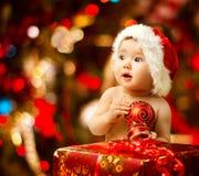 圣诞老人帽子的圣诞节婴孩在红色当前礼物盒附近 免版税库存图片