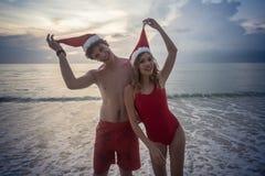 戴圣诞老人帽子的夫妇在海滩 库存照片