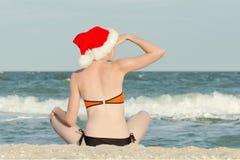 圣诞老人帽子的女孩与在后面的题字新年是s 免版税库存图片
