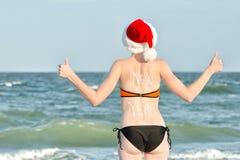 圣诞老人帽子的女孩与在后面的题字新年 免版税库存照片
