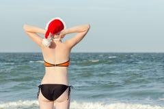 圣诞老人帽子的女孩与在后面的题字新年 Ha 图库摄影