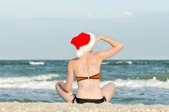 圣诞老人帽子的女孩与在后面sitt的题字新年 库存照片