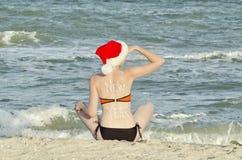 圣诞老人帽子的女孩与在后面sitt的题字新年 库存图片