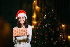 圣诞老人帽子的女孩在与礼物的一棵圣诞树附近 免版税库存照片