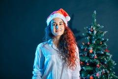 圣诞老人帽子的女孩在与礼物的一棵圣诞树附近 库存照片