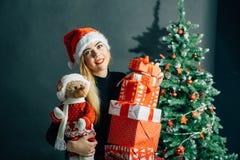 圣诞老人帽子的女孩在与礼物的一棵圣诞树附近 免版税库存图片