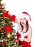 圣诞老人帽子的女孩在圣诞树附近。 免版税库存照片