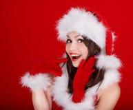 圣诞老人帽子的女孩在红色背景。 免版税库存图片