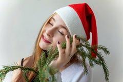 圣诞老人帽子的女孩有圣诞节绿色冷杉的分支 库存照片