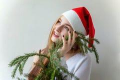 圣诞老人帽子的女孩有圣诞节绿色冷杉的分支 免版税库存图片