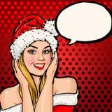 圣诞老人帽子的女孩有在红色背景的讲话泡影的 库存照片