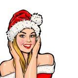 圣诞老人帽子的女孩有在红色背景的讲话泡影的 库存图片