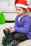 圣诞老人帽子的女孩有彩色小灯的 免版税库存图片