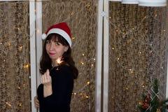 圣诞老人帽子的女孩有闪烁发光物的 免版税库存照片