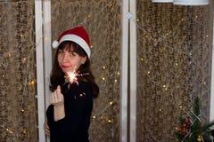 圣诞老人帽子的女孩有闪烁发光物的 图库摄影