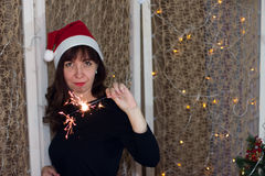 圣诞老人帽子的女孩有闪烁发光物的 免版税库存图片