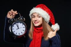 圣诞老人帽子的女孩有闹钟的 免版税库存照片