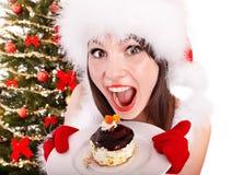 圣诞老人帽子的女孩由圣诞树吃蛋糕。 免版税图库摄影