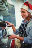 戴圣诞老人帽子的女服务员侧视图的综合图象使用浓咖啡制造商 免版税库存照片