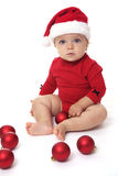 戴圣诞老人帽子的女婴,使用与红色球 免版税库存图片