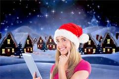 圣诞老人帽子的妇女使用数字式片剂 免版税图库摄影