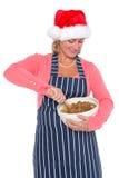 戴圣诞老人帽子的妇女做圣诞节蛋糕 库存图片