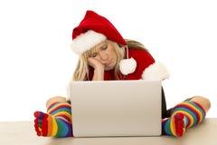 圣诞老人帽子的妇女和与膝上型计算机睡觉的色的袜子 免版税库存照片