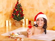 圣诞老人帽子的妇女在浴放松。 免版税库存图片
