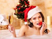 圣诞老人帽子的妇女在浴放松。 图库摄影