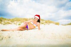 圣诞老人帽子的妇女在海滩 库存图片