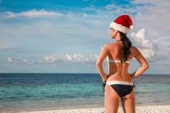 圣诞老人帽子的妇女在海滩 免版税库存照片